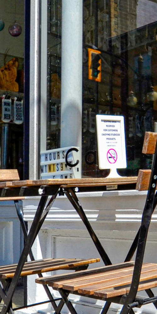 A small table and two chairs outside a cafe