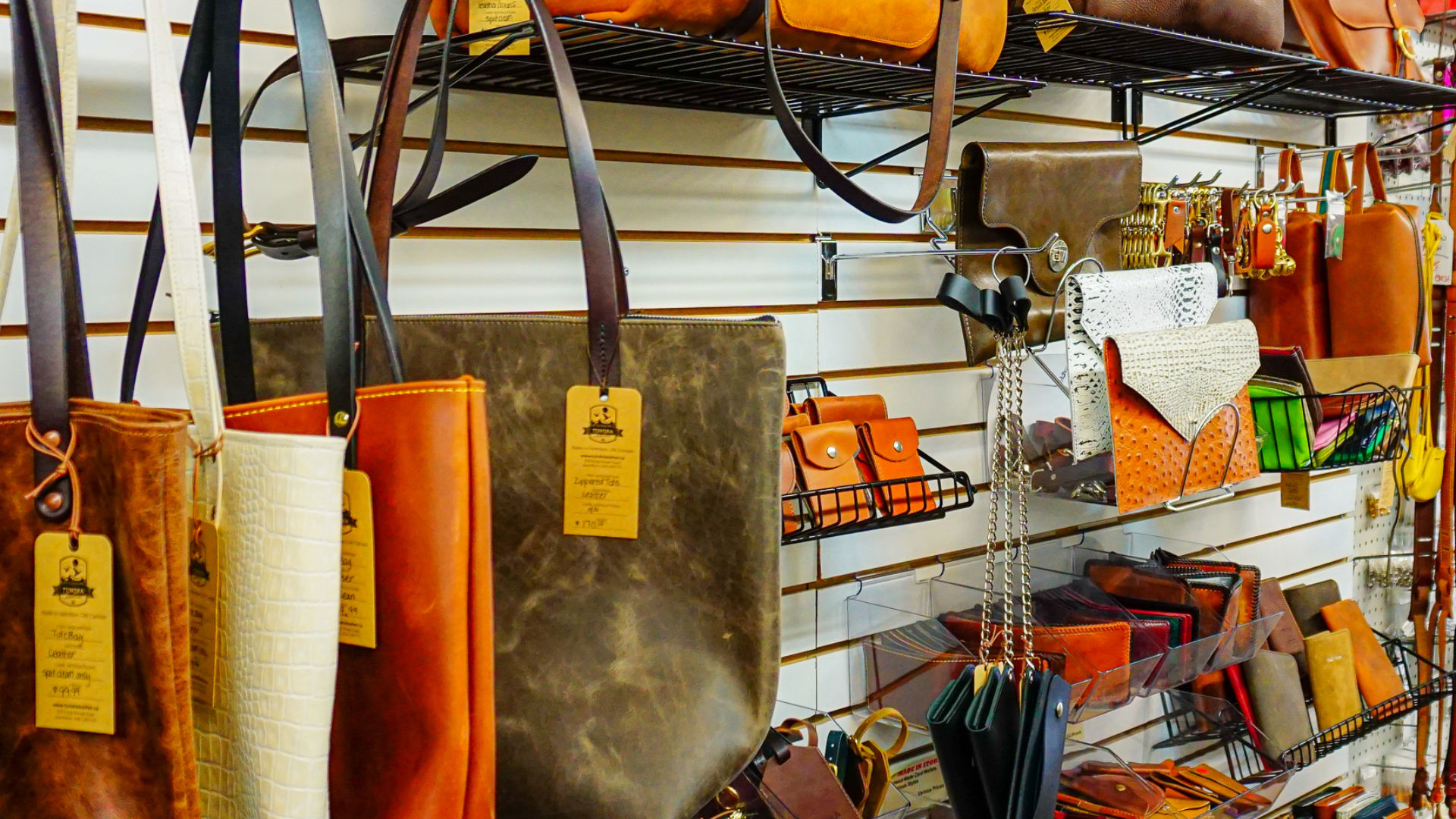 A rack of hand made leather bags, purses, and wallets
