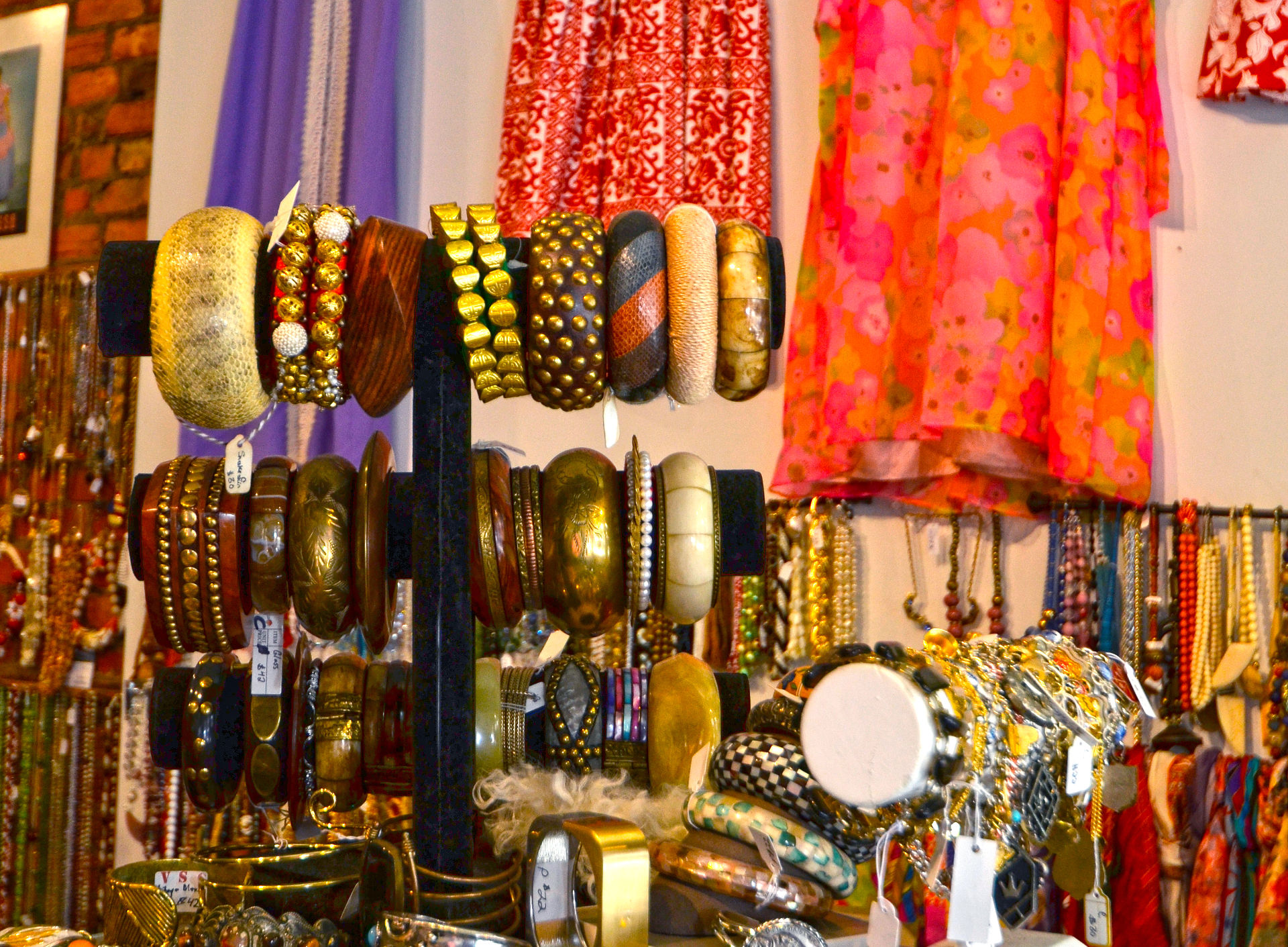 A number of wood and metal bracelets on a rack with bright fabrics and racks of necklaces in the background at VintageSoulGeek