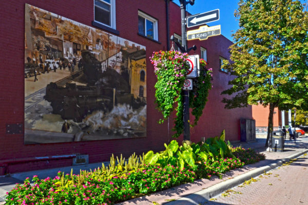 View of mural and city gardens at the corner of King Street and Ferguson, across from the Black Forest Inn Biergarten patio.
