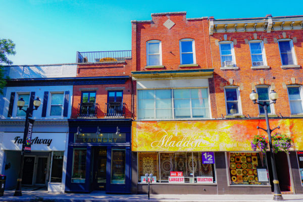 View of Fade Away tattoo removal, The Laundry Design Works and Aladdin's Carpet store, on King Street East