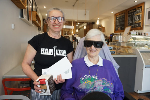 Mina Falcone with customer inside of Cafe Oranje