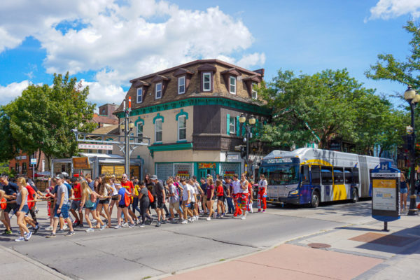 Students pulling a bus down King Street during frosh week.