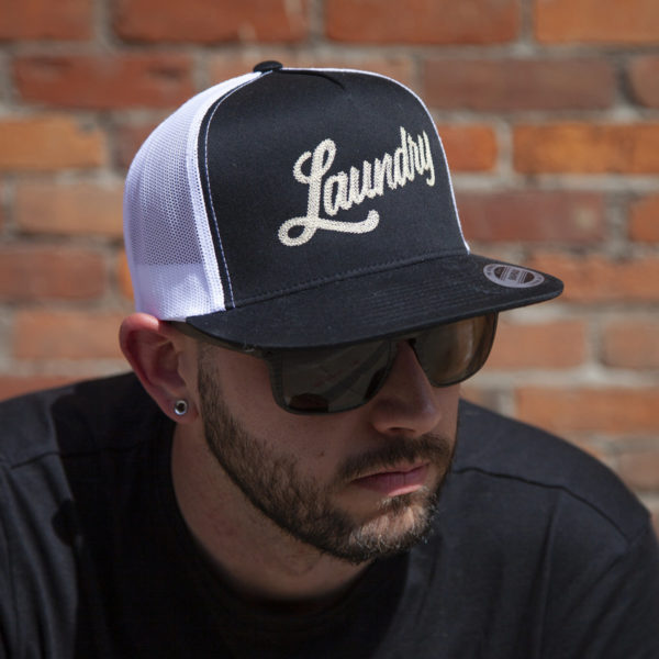 Man wearing sunglasses and a classic black snapback style hat, adorned with premium quality pearl stitched embroidered logo