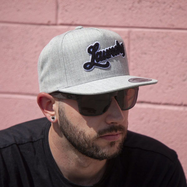 Man wearing sunglasses and a melange gray snap-back style hat embellished with an old-school felted Laundry patch