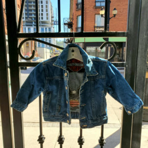 Front View of a toddler sized Vintage Harley Davidson Denim Jacket hanging on an iron gate