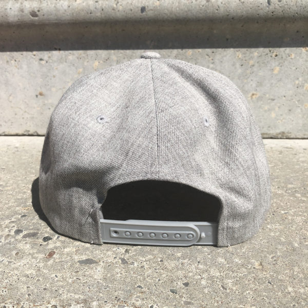 rear view of a melange gray snap-back style hat embellished with an old-school felted Laundry patch