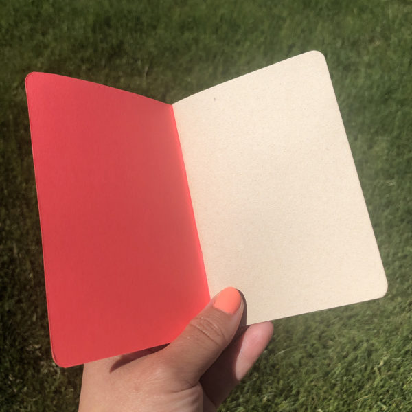 Hand holding open a pink pocket notebook