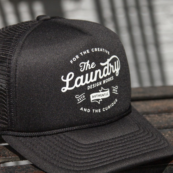 Close up of a black retro foam trucker hat featuring a retro style Laundry Design Works logo graphic