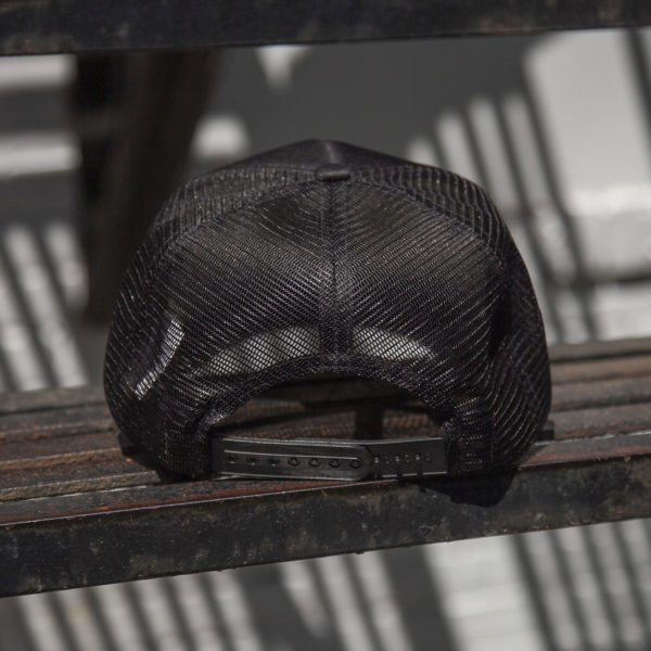 Rear view of a black retro foam trucker hat featuring a retro style Laundry Design Works logo graphic