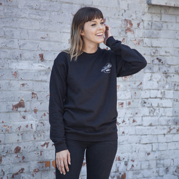 Woman wearing a fleece crew neck sweater with a screen printed, typography based graphic on the left chest