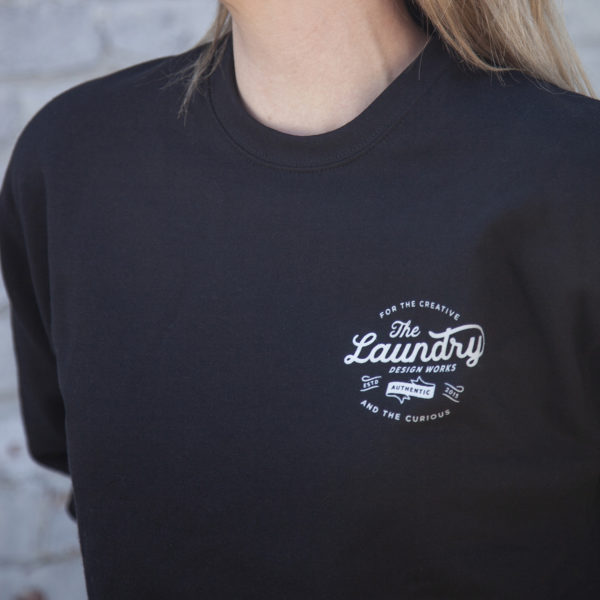 Close up of a Woman wearing a fleece crew neck sweater with a screen printed, typography based graphic on the left chest