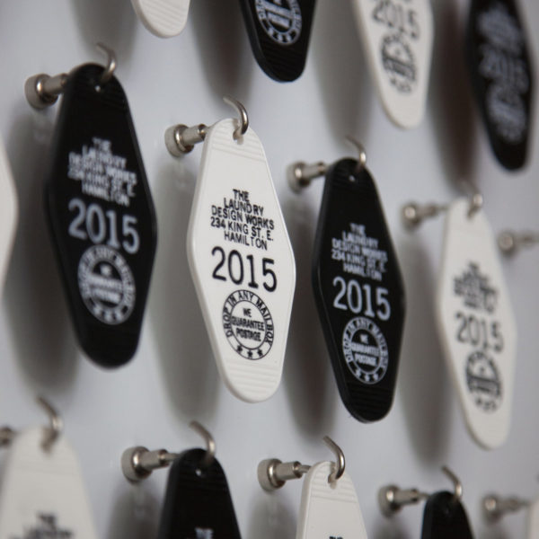 Close up of a bunch of retro style motel keychains imprinted with Laundry graphics hanging from hooks on a wall