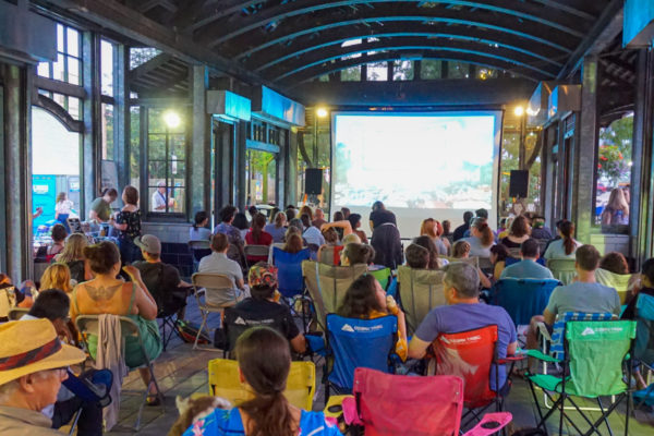 2019 movie night at Ferguson Station. Group of people sitting together watching a movie on a projector screen, while enjoying snacks.