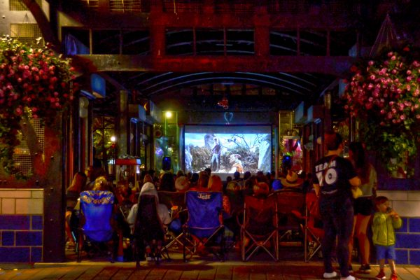 2018 movie night at Ferguson Station. Group of people watching a movie on a projector views from King Street.