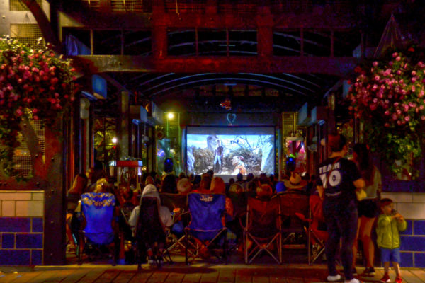 View of Movie night at Ferguson Station. Group of people watching a movie on a projector.