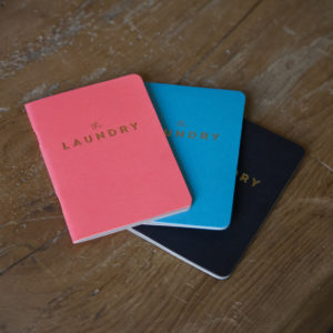 "3 Pocket notebooks coloured pink, blue, and black with gold text that reads ""The Laundry"" arranged on a wooden table"
