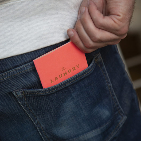 """A pink pocket notebook with gold text that reads """"The Laundry"""" being placed in a persons back pocket"""
