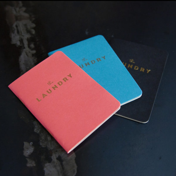 """3 Pocket notebooks coloured pink, blue, and black with gold text that reads """"The Laundry"""" arranged on a marble table"""