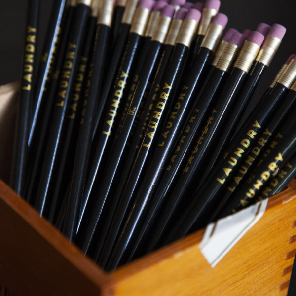"""A bunch of black pencils with gold text that reads """"The Laundry"""" standing in a wooden box"""