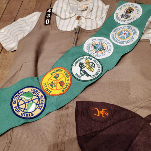 A 1970/80's vintage Official Girl Scout uniform laying on a wood table