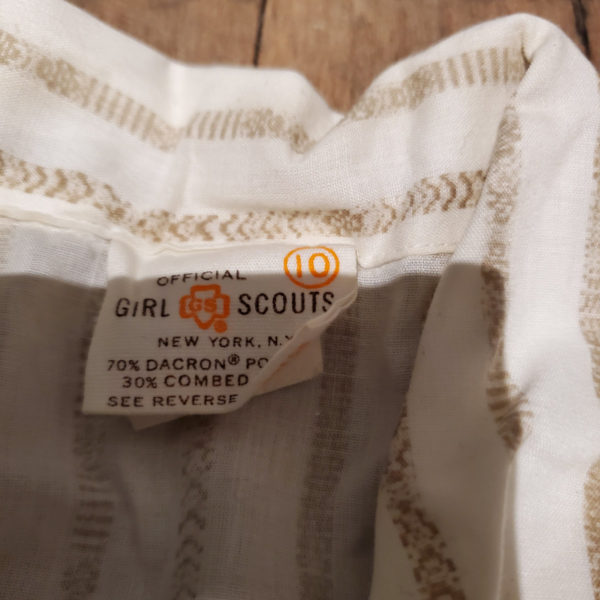 """Close up of the tag on a A 1970/80's vintage Official Girl Scout uniform reading """"Official Girl Scouts New york, N.Y."""""""