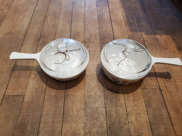 Vintage Corningware Country Festival Skillet 1975 with lids on a wooden floor