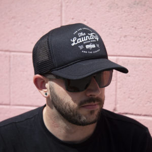 Man wearing sunglasses and a black retro foam trucker hat featuring a retro style Laundry Design Works logo graphic