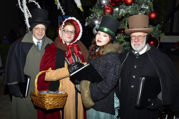 2018 Victorian Night. Carollers posing for a picture in front of a holiday display.