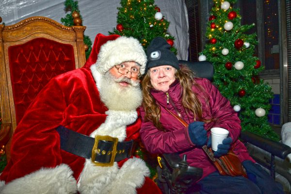 2018 Victorian Night. Woman posing for a picture with Santa, while enjoying hot chocolate.