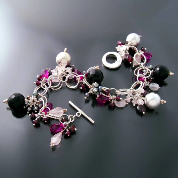 One-of-a-kind bracelet laying on a black tabletop, featuring a decadent combination of sterling silver, black onyx, Freshwater pearls, Garnet, Rose Quartz, and Swarovski crystals.