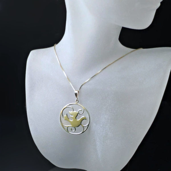 Yellow Gold Dove Pendant on a chain hanging around a female mannequins neck. This graceful medallion pendant is sure to become a family heirloom. Featuring a lovely Dove design surrounded by vines.