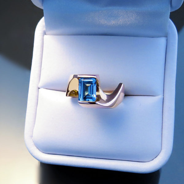 Modern Blue Topaz Ring in 14K Yellow Gold sitting in a white ring box.