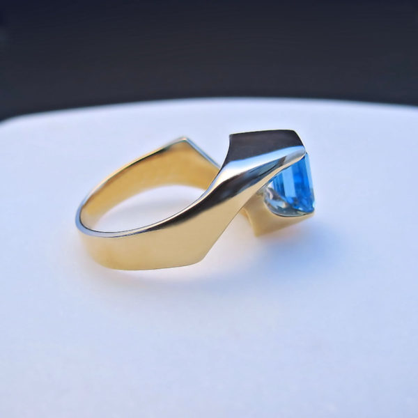 Modern Blue Topaz Ring in 14K Yellow Gold. An emerald cut blue topaz appears to float in this unique setting.