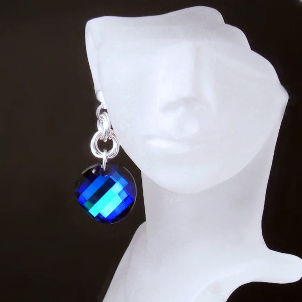 One single Electric blue Swarovski crystal Statement Earring on the right side of a female mannequin heads ear. Handmade in sterling silver.