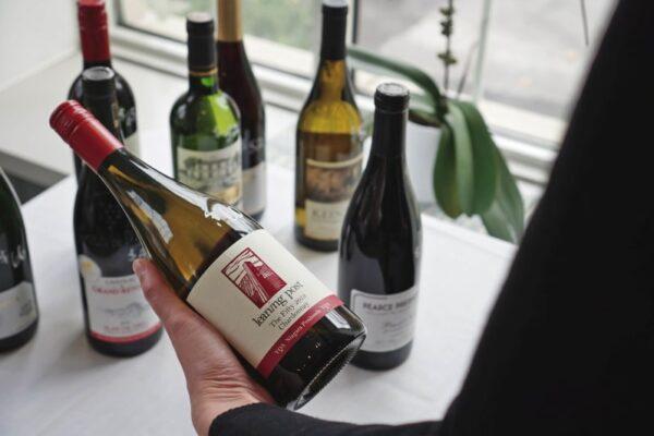 Person holding wine bottle at Seasoned Restaurant