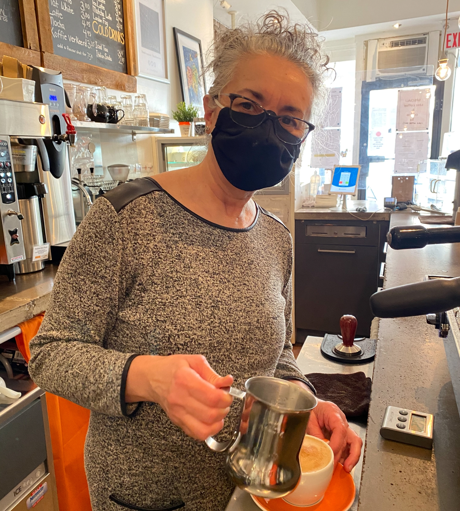Mina owner of Cafe Oranje pouring a coffee - International Women's Day
