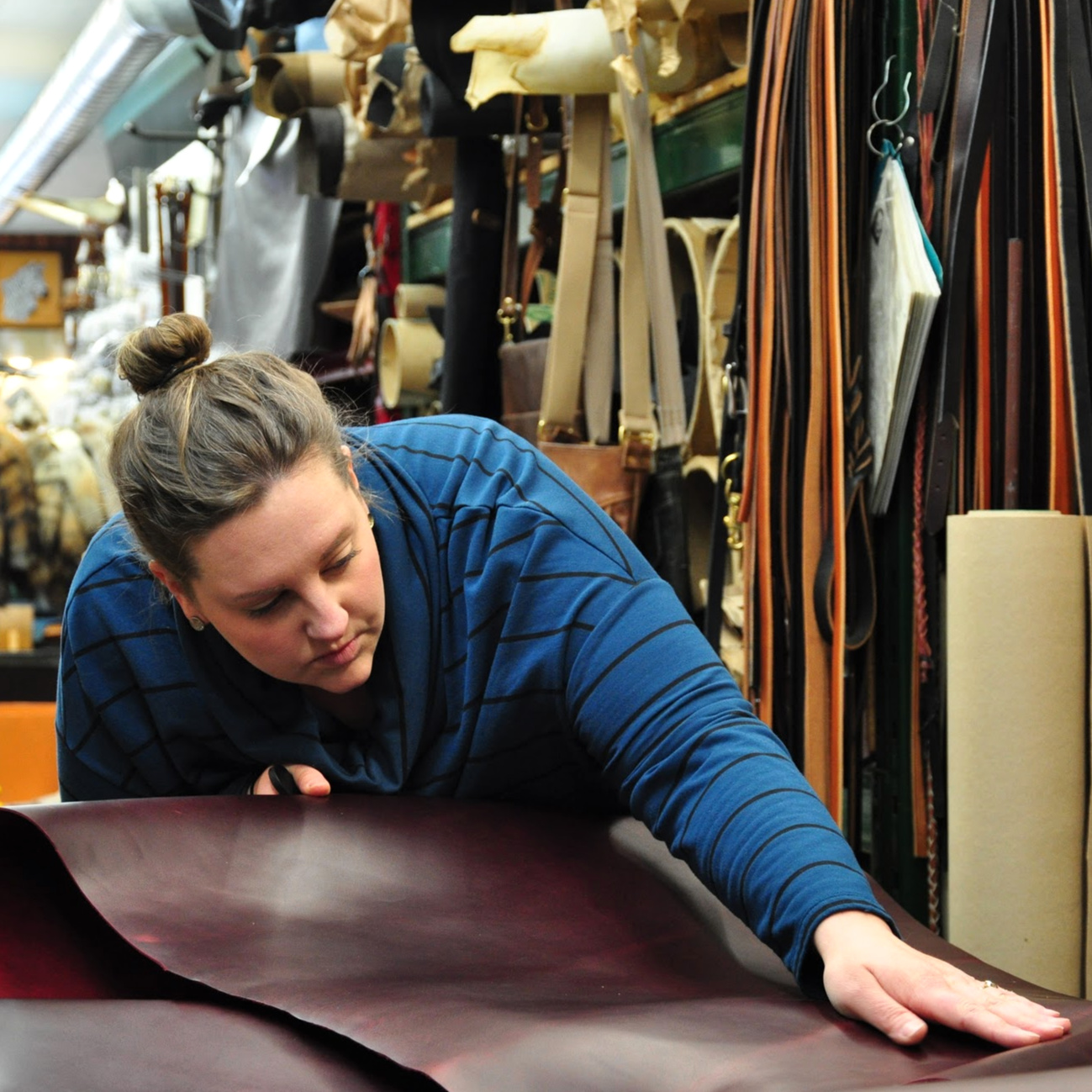 Image of Kristi owner of tundra leather working with a piece of leather - International Women's Day