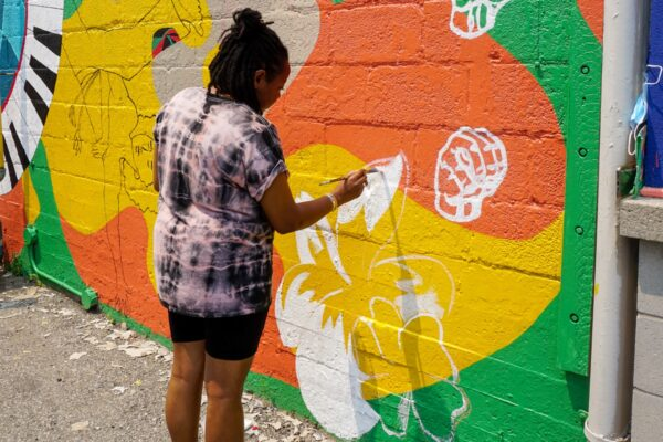 Person painting new mural at 205 King St. East